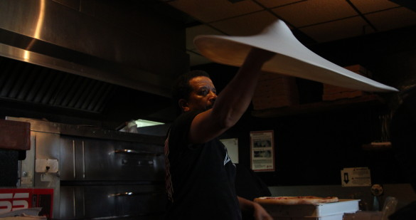 """A chef at The Spinning Pie (aka """"Spin"""") restaurant in Castleberry Hill tosses a pizza in front of customers. Various specialty pizzas like the Caribbean Jerk Chicken pizza are offered at Spin.  Photo by Ralph Hernandez 